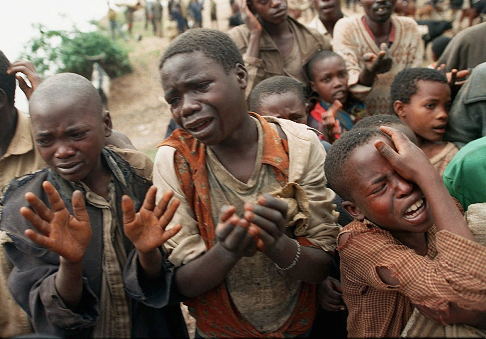 **FILE** Rwandan refugee children plead with Zairean soldiers to allow them across a bridge separating Rwanda and Zaire where their mothers had crossed moments earlier before the soldiers closed the border in this Aug. 20, 1994 file photo. At least 500,000 people were killed in the genocide in Rwanda, 13 years ago. (AP Photo/Jean-Marc Bouju, file)