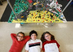 Kaitlyn Gallaway, left, Samuel Knotts, and Sarah Schmidt, fourth-grade students at Agnor-Hurt Elementary School in Charlottesville, Va., are shown with the World Peace Game. Knotts, 10, played a prime minister in a recent scenario, and Schmidt, 9, was a diplomat and saboteur. Illustrates SCHOOLS-PEACE (category l), by Susan Svrluga (c) 2012, The Washington Post. Moved Friday, April 20, 2012. (MUST CREDIT: Photo for The Washington Post by Norm Shafer)