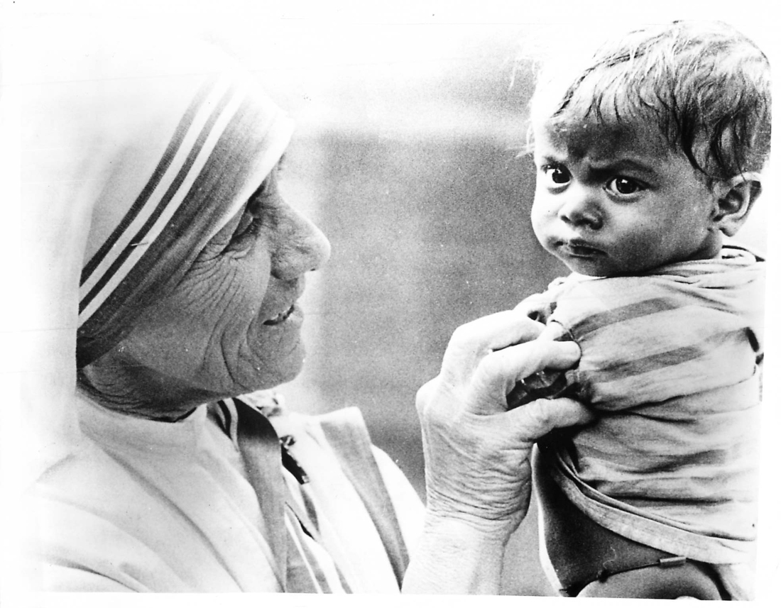 """(1977) Mother Teresa of Calcutta, shown with an Indian child, worked to help sick and homeless victims in the cyclone-ravaged Indian state of Andhra Pradesh. She said her Missionaries of Charity nuns have """"all the experience necessary to work in this disaster area because of previous efforts during floods."""" """"In all these human tragedies, God is trying to teach us something. We are not able to understand Him,"""" she said as she went about supervising the rescue operation. Religion News Service file photo"""